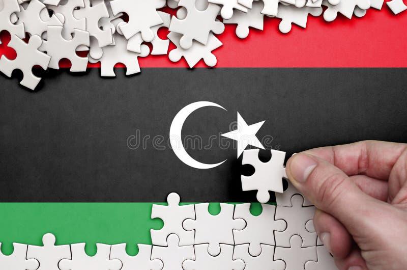 Η σημαία της Λιβύης απεικονίζεται σε έναν πίνακα στον οποίο το ανθρώπινο χέρι διπλώνει έναν γρίφο του άσπρου χρώματος στοκ εικόνα
