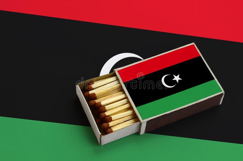Η σημαία της Λιβύης παρουσιάζεται σε ένα ανοικτό σπιρτόκουτο, το οποίο γεμίζουν με τις αντιστοιχίες και βρίσκεται σε μια μεγάλη σ στοκ εικόνα με δικαίωμα ελεύθερης χρήσης