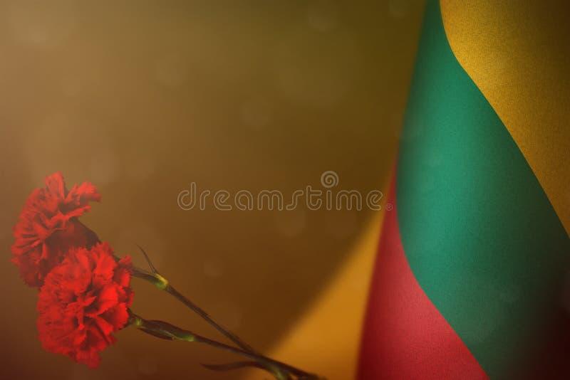 Η σημαία της Λιθουανίας για την τιμή των παλαιμάχων ή της ημέρας μνήμης με το κόκκινο γαρίφαλο δύο ανθίζει Δόξα στους ήρωες της Λ στοκ φωτογραφία