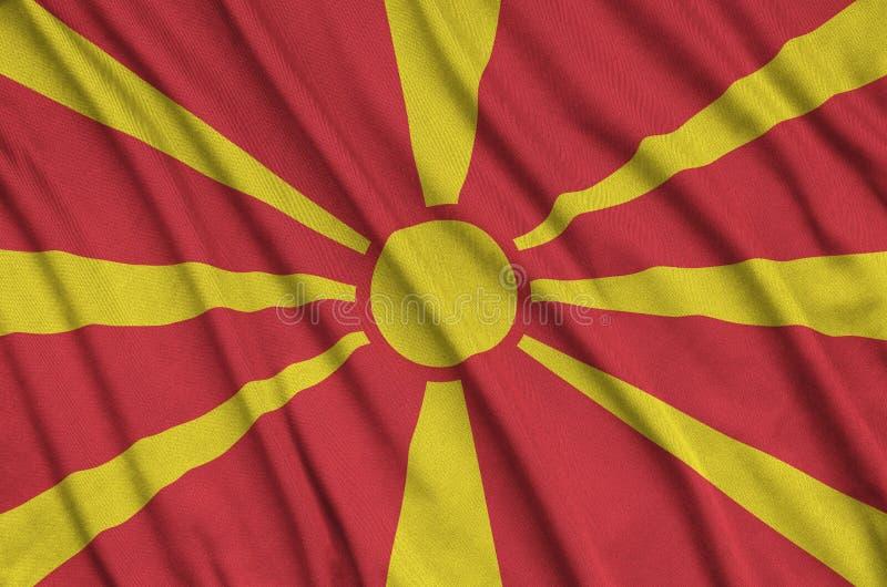 Η σημαία της Μακεδονίας απεικονίζεται σε ένα ύφασμα αθλητικών υφασμάτων με πολλές πτυχές Έμβλημα αθλητικών ομάδων στοκ εικόνα με δικαίωμα ελεύθερης χρήσης