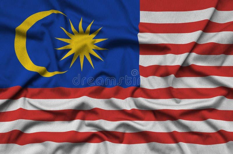 Η σημαία της Μαλαισίας απεικονίζεται σε ένα ύφασμα αθλητικών υφασμάτων με πολλές πτυχές Έμβλημα αθλητικών ομάδων στοκ φωτογραφία