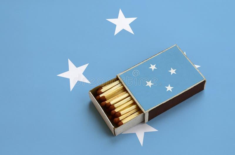 Η σημαία της Μικρονησίας παρουσιάζεται σε ένα ανοικτό σπιρτόκουτο, το οποίο γεμίζουν με τις αντιστοιχίες και βρίσκεται σε μια μεγ στοκ εικόνες