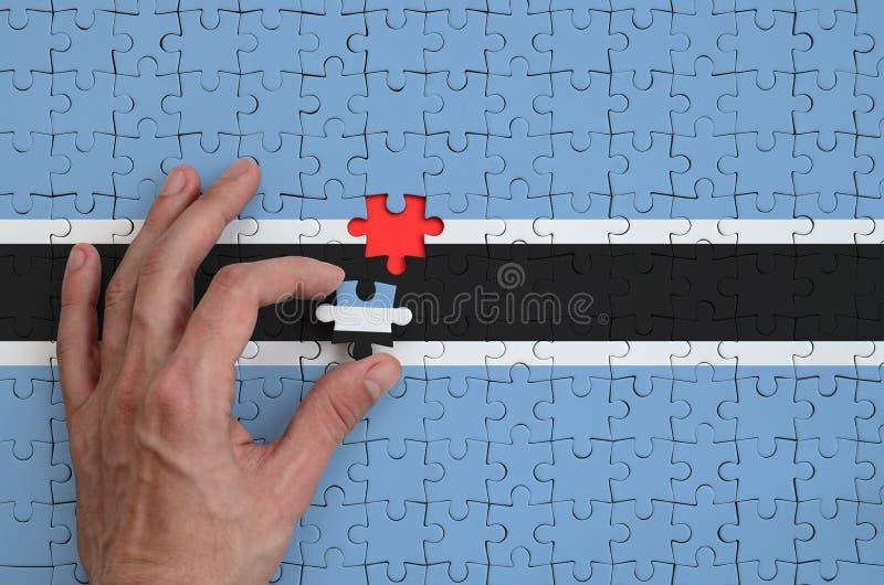 Η σημαία της Μποτσουάνα απεικονίζεται σε έναν γρίφο, τον οποίο το χέρι ατόμων ` s ολοκληρώνει για να διπλώσει στοκ εικόνες