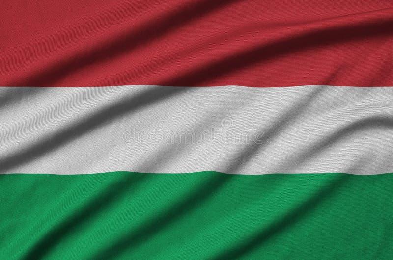 Η σημαία της Ουγγαρίας απεικονίζεται σε ένα ύφασμα αθλητικών υφασμάτων με πολλές πτυχές Έμβλημα αθλητικών ομάδων στοκ εικόνα