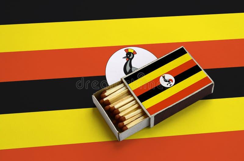 Η σημαία της Ουγκάντας παρουσιάζεται σε ένα ανοικτό σπιρτόκουτο, το οποίο γεμίζουν με τις αντιστοιχίες και βρίσκεται σε μια μεγάλ στοκ εικόνες
