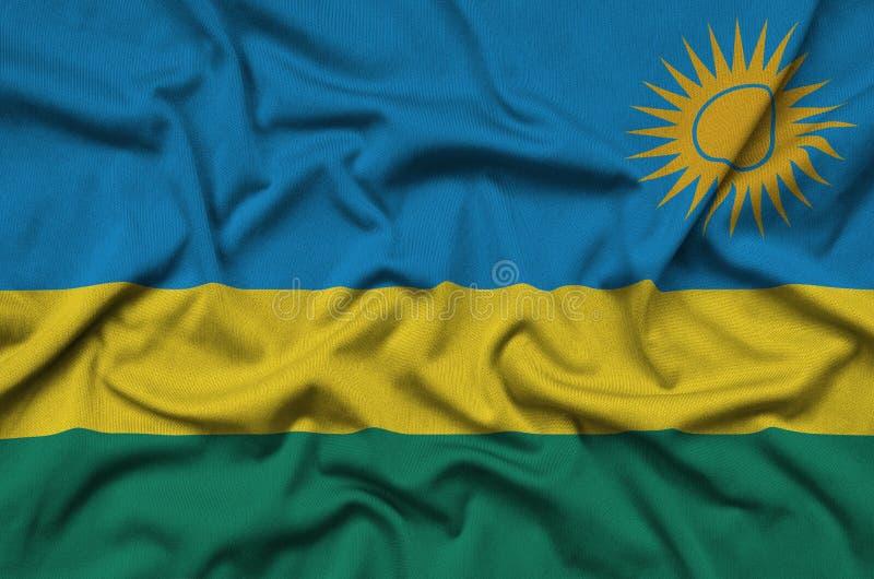 Η σημαία της Ρουάντα απεικονίζεται σε ένα ύφασμα αθλητικών υφασμάτων με πολλές πτυχές Έμβλημα αθλητικών ομάδων στοκ φωτογραφίες