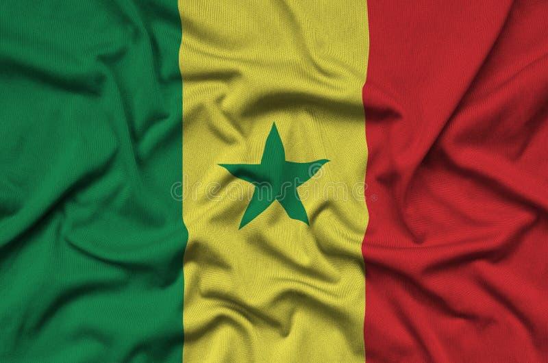 Η σημαία της Σενεγάλης απεικονίζεται σε ένα ύφασμα αθλητικών υφασμάτων με πολλές πτυχές Έμβλημα αθλητικών ομάδων στοκ εικόνες