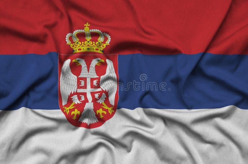 Η σημαία της Σερβίας απεικονίζεται σε ένα ύφασμα αθλητικών υφασμάτων με πολλές πτυχές Έμβλημα αθλητικών ομάδων στοκ εικόνες