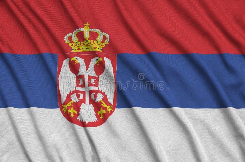 Η σημαία της Σερβίας απεικονίζεται σε ένα ύφασμα αθλητικών υφασμάτων με πολλές πτυχές Έμβλημα αθλητικών ομάδων στοκ φωτογραφία με δικαίωμα ελεύθερης χρήσης
