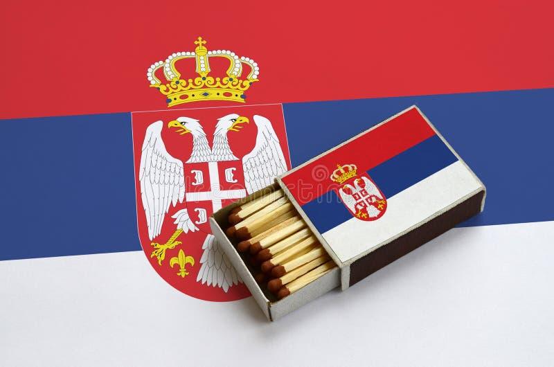 Η σημαία της Σερβίας παρουσιάζεται σε ένα ανοικτό σπιρτόκουτο, το οποίο γεμίζουν με τις αντιστοιχίες και βρίσκεται σε μια μεγάλη  στοκ φωτογραφία