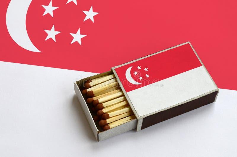 Η σημαία της Σιγκαπούρης παρουσιάζεται σε ένα ανοικτό σπιρτόκουτο, το οποίο γεμίζουν με τις αντιστοιχίες και βρίσκεται σε μια μεγ στοκ εικόνα με δικαίωμα ελεύθερης χρήσης