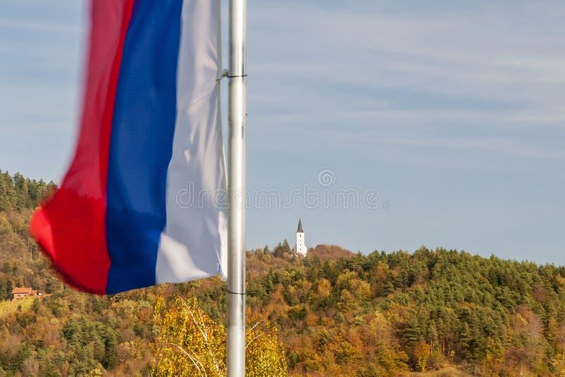 Η σημαία της Σλοβενίας κυματίζει σε ένα όμορφο φθινοπωρινό υπόβαθρο στη Ζρέτσε στοκ φωτογραφία με δικαίωμα ελεύθερης χρήσης