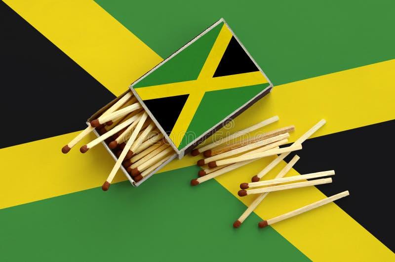Η σημαία της Τζαμάικας παρουσιάζεται σε ένα ανοικτό σπιρτόκουτο, από το οποίο διάφορες αντιστοιχίες αφορούν και βρίσκονται μια με στοκ εικόνες