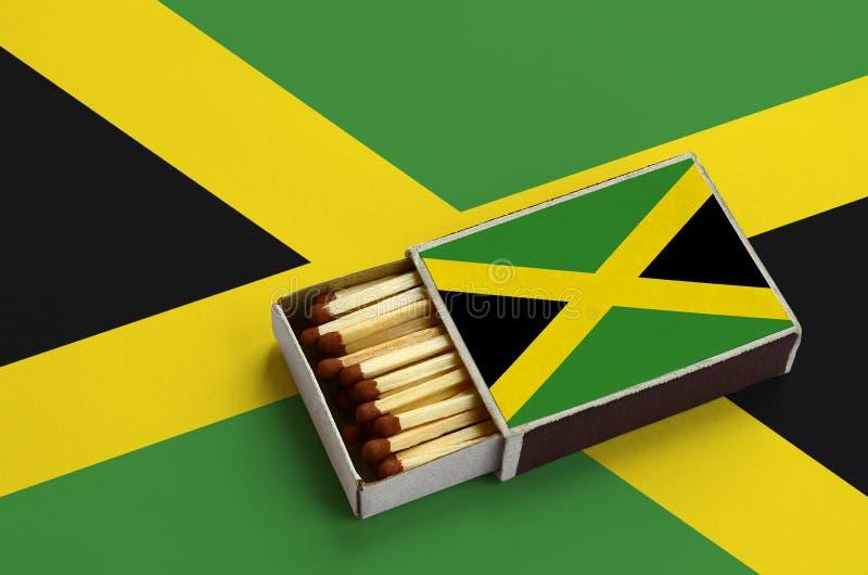 Η σημαία της Τζαμάικας παρουσιάζεται σε ένα ανοικτό σπιρτόκουτο, το οποίο γεμίζουν με τις αντιστοιχίες και βρίσκεται σε μια μεγάλ στοκ φωτογραφία με δικαίωμα ελεύθερης χρήσης