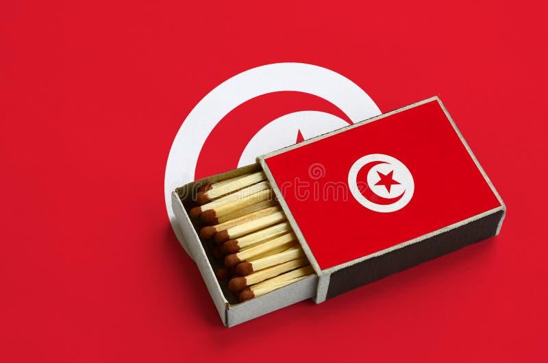 Η σημαία της Τυνησίας παρουσιάζεται σε ένα ανοικτό σπιρτόκουτο, το οποίο γεμίζουν με τις αντιστοιχίες και βρίσκεται σε μια μεγάλη στοκ εικόνα