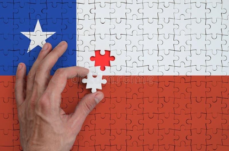 Η σημαία της Χιλής απεικονίζεται σε έναν γρίφο, τον οποίο το χέρι ατόμων ` s ολοκληρώνει για να διπλώσει στοκ εικόνα