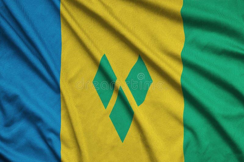 Η σημαία του Άγιου Βικεντίου και Γρεναδίνες απεικονίζεται σε ένα ύφασμα αθλητικών υφασμάτων με πολλές πτυχές Έμβλημα αθλητικών ομ στοκ φωτογραφία με δικαίωμα ελεύθερης χρήσης