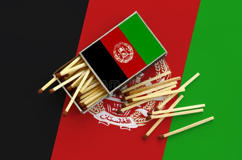 Η σημαία του Αφγανιστάν παρουσιάζεται σε ένα ανοικτό σπιρτόκουτο, από το οποίο διάφορες αντιστοιχίες αφορούν και βρίσκονται μια μ στοκ φωτογραφία
