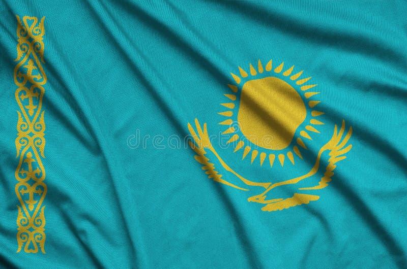 Η σημαία του Καζακστάν απεικονίζεται σε ένα ύφασμα αθλητικών υφασμάτων με πολλές πτυχές Έμβλημα αθλητικών ομάδων στοκ εικόνες