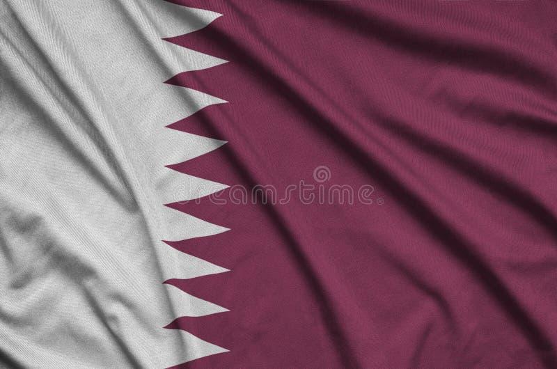 Η σημαία του Κατάρ απεικονίζεται σε ένα ύφασμα αθλητικών υφασμάτων με πολλές πτυχές Έμβλημα αθλητικών ομάδων στοκ φωτογραφίες