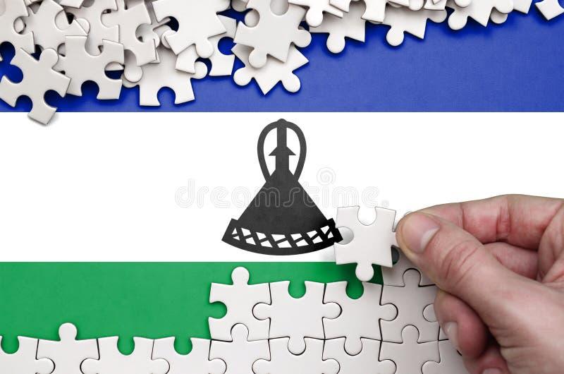 Η σημαία του Λεσόθο απεικονίζεται σε έναν πίνακα στον οποίο το ανθρώπινο χέρι διπλώνει έναν γρίφο του άσπρου χρώματος στοκ φωτογραφίες