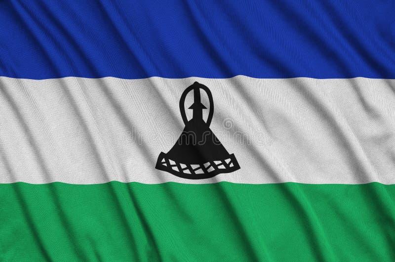 Η σημαία του Λεσόθο απεικονίζεται σε ένα ύφασμα αθλητικών υφασμάτων με πολλές πτυχές Έμβλημα αθλητικών ομάδων στοκ φωτογραφίες