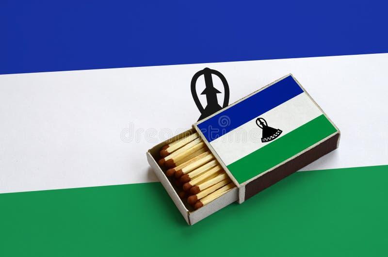 Η σημαία του Λεσόθο παρουσιάζεται σε ένα ανοικτό σπιρτόκουτο, το οποίο γεμίζουν με τις αντιστοιχίες και βρίσκεται σε μια μεγάλη σ στοκ εικόνα με δικαίωμα ελεύθερης χρήσης