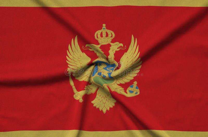 Η σημαία του Μαυροβουνίου απεικονίζεται σε ένα ύφασμα αθλητικών υφασμάτων με πολλές πτυχές Έμβλημα αθλητικών ομάδων στοκ εικόνες