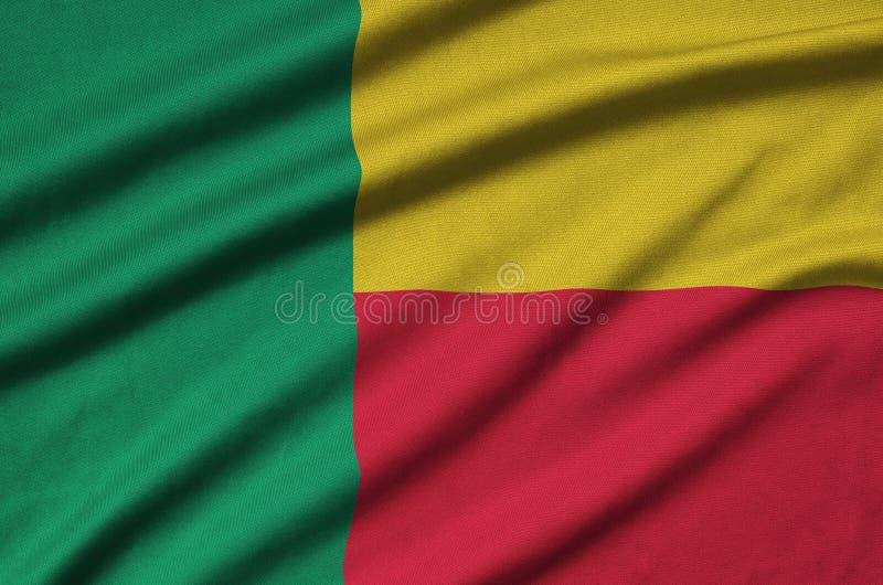 Η σημαία του Μπενίν απεικονίζεται σε ένα ύφασμα αθλητικών υφασμάτων με πολλές πτυχές Έμβλημα αθλητικών ομάδων στοκ εικόνα με δικαίωμα ελεύθερης χρήσης