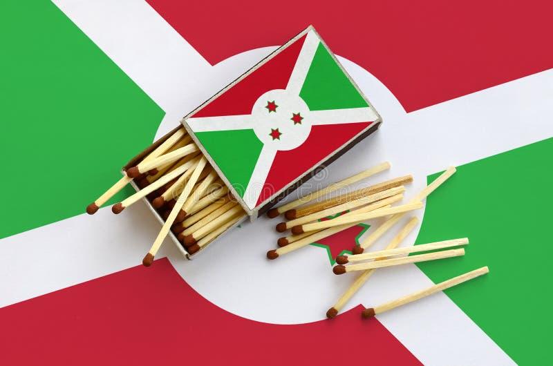 Η σημαία του Μπουρούντι παρουσιάζεται σε ένα ανοικτό σπιρτόκουτο, από το οποίο διάφορες αντιστοιχίες αφορούν και βρίσκονται μια μ στοκ φωτογραφία