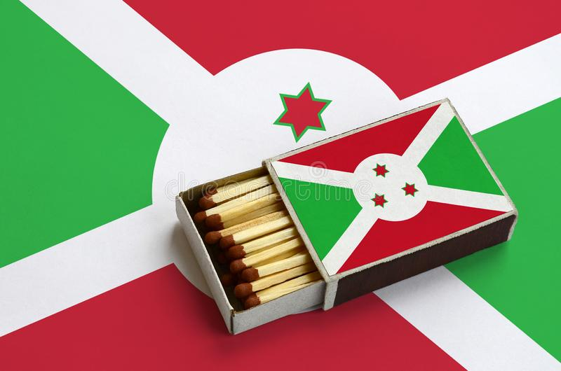 Η σημαία του Μπουρούντι παρουσιάζεται σε ένα ανοικτό σπιρτόκουτο, το οποίο γεμίζουν με τις αντιστοιχίες και βρίσκεται σε μια μεγά στοκ εικόνες