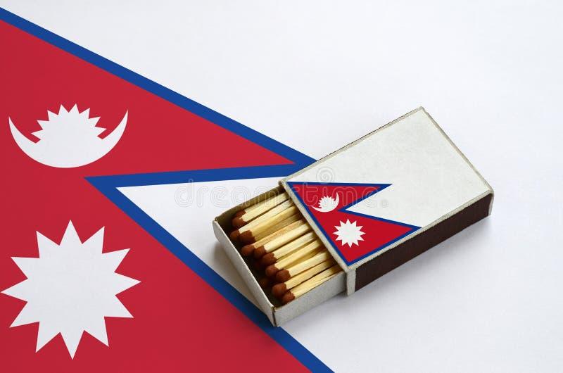 Η σημαία του Νεπάλ παρουσιάζεται σε ένα ανοικτό σπιρτόκουτο, το οποίο γεμίζουν με τις αντιστοιχίες και βρίσκεται σε μια μεγάλη ση στοκ εικόνα