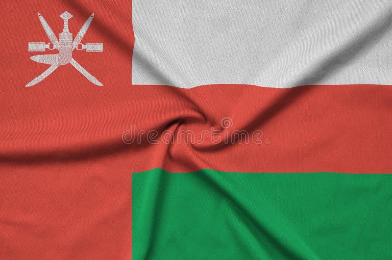 Η σημαία του Ομάν απεικονίζεται σε ένα ύφασμα αθλητικών υφασμάτων με πολλές πτυχές Έμβλημα αθλητικών ομάδων στοκ φωτογραφίες