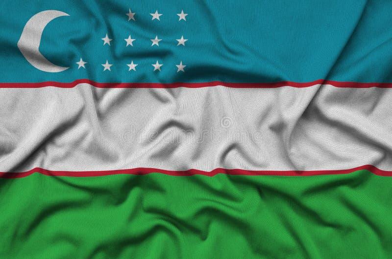 Η σημαία του Ουζμπεκιστάν απεικονίζεται σε ένα ύφασμα αθλητικών υφασμάτων με πολλές πτυχές Έμβλημα αθλητικών ομάδων στοκ φωτογραφία
