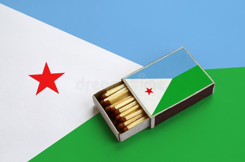 Η σημαία του Τζιμπουτί παρουσιάζεται σε ένα ανοικτό σπιρτόκουτο, το οποίο γεμίζουν με τις αντιστοιχίες και βρίσκεται σε μια μεγάλ στοκ εικόνες