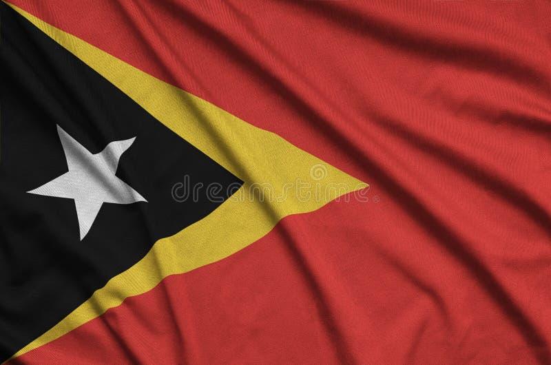 Η σημαία του Τιμόρ Leste απεικονίζεται σε ένα ύφασμα αθλητικών υφασμάτων με πολλές πτυχές Έμβλημα αθλητικών ομάδων στοκ εικόνα με δικαίωμα ελεύθερης χρήσης