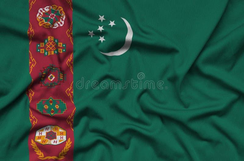 Η σημαία του Τουρκμενιστάν απεικονίζεται σε ένα ύφασμα αθλητικών υφασμάτων με πολλές πτυχές Έμβλημα αθλητικών ομάδων στοκ εικόνα με δικαίωμα ελεύθερης χρήσης