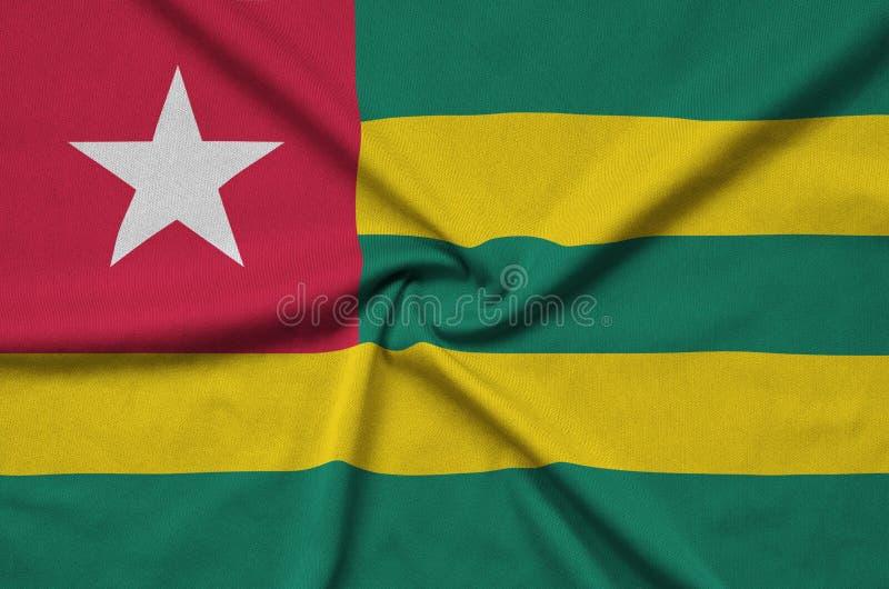 Η σημαία του Τόγκο απεικονίζεται σε ένα ύφασμα αθλητικών υφασμάτων με πολλές πτυχές Έμβλημα αθλητικών ομάδων στοκ φωτογραφία με δικαίωμα ελεύθερης χρήσης