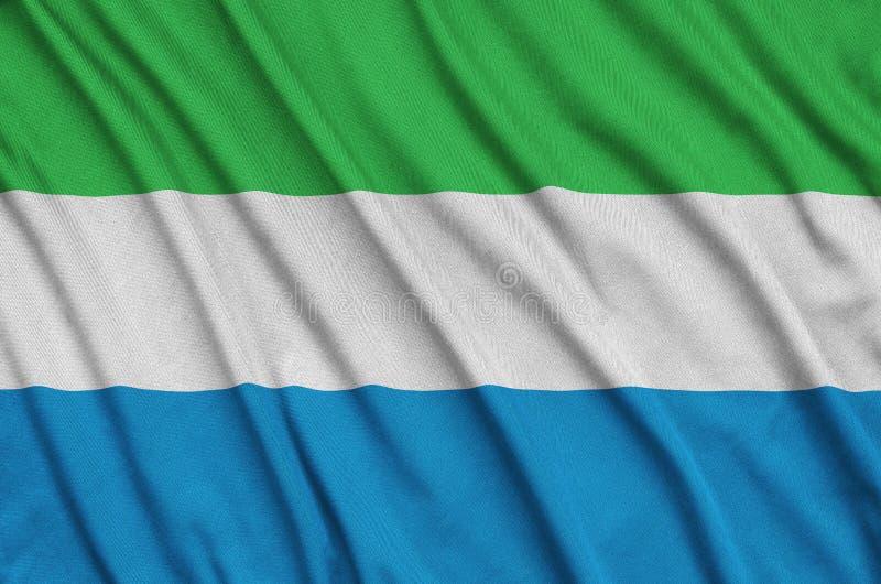 Η σημαία του Sierra Leone απεικονίζεται σε ένα ύφασμα αθλητικών υφασμάτων με πολλές πτυχές Έμβλημα αθλητικών ομάδων στοκ φωτογραφία