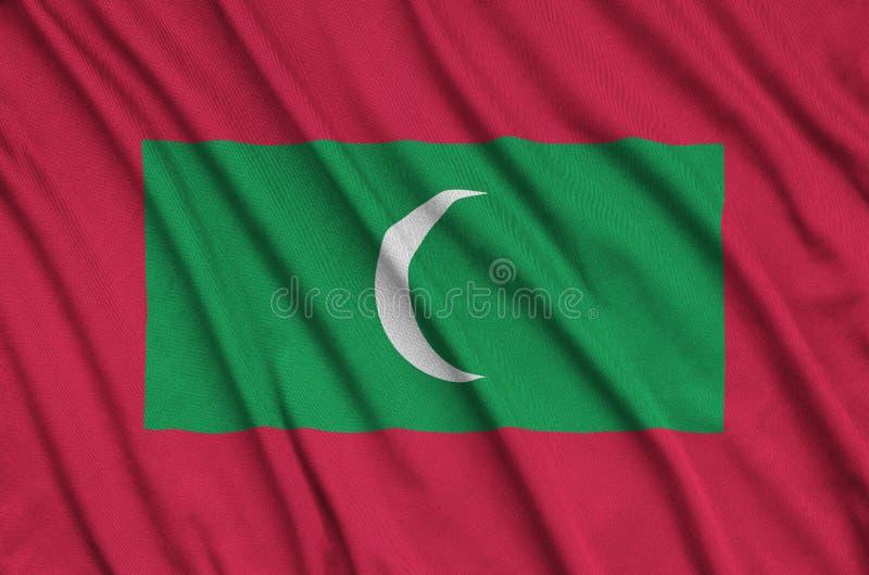 Η σημαία των Μαλδίβες απεικονίζεται σε ένα ύφασμα αθλητικών υφασμάτων με πολλές πτυχές Έμβλημα αθλητικών ομάδων στοκ εικόνες
