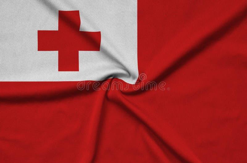 Η σημαία των Τόνγκα απεικονίζεται σε ένα ύφασμα αθλητικών υφασμάτων με πολλές πτυχές Έμβλημα αθλητικών ομάδων στοκ εικόνα με δικαίωμα ελεύθερης χρήσης