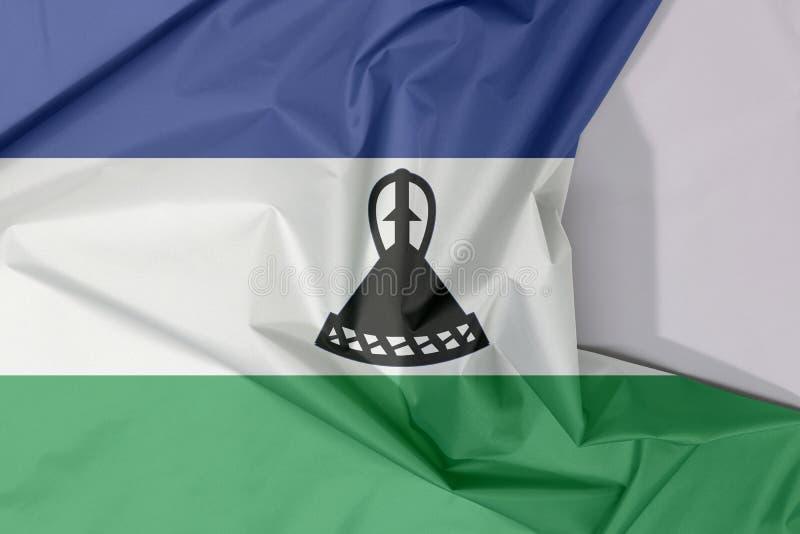 Η σημαία υφάσματος του Λεσόθο crepe και ζαρώνει με το άσπρο διάστημα στοκ φωτογραφίες