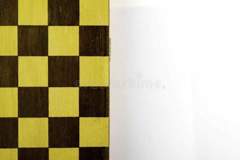 Η σκακιέρα βρίσκεται σε ένα άσπρο υπόβαθρο, διάστημα αντιγράφων στοκ εικόνα