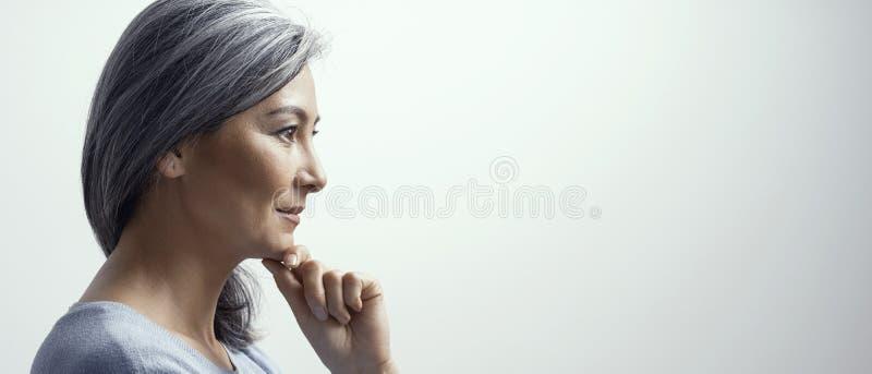 Η σκεπτική γυναίκα αγγίζει το πηγούνι και ελαφρώς τα χαμόγελα στοκ φωτογραφίες