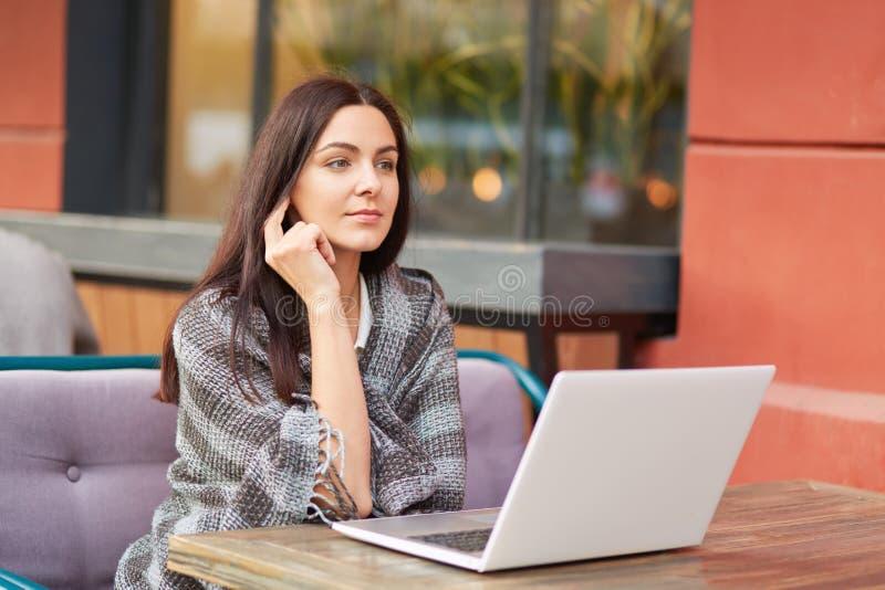 Η σκεπτική μελαχροινή μαλλιαρή γυναίκα που τυλίγεται στο coverlet, χρησιμοποιεί την ηλεκτρονική συσκευή, προσέχει τα webinar ή su στοκ φωτογραφία