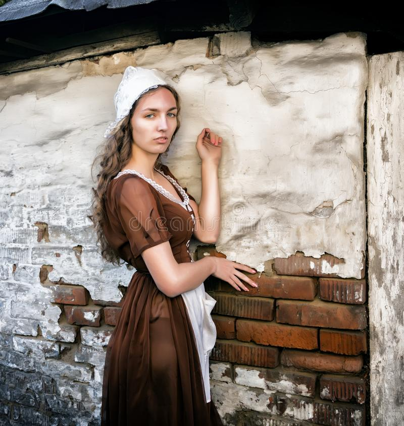 Η σκεπτική νέα γυναίκα σε ένα αγροτικό φόρεμα που στέκεται κοντά στον παλαιό τουβλότοιχο στο παλαιό σπίτι αισθάνεται μόνη Ύφος Ci στοκ φωτογραφία