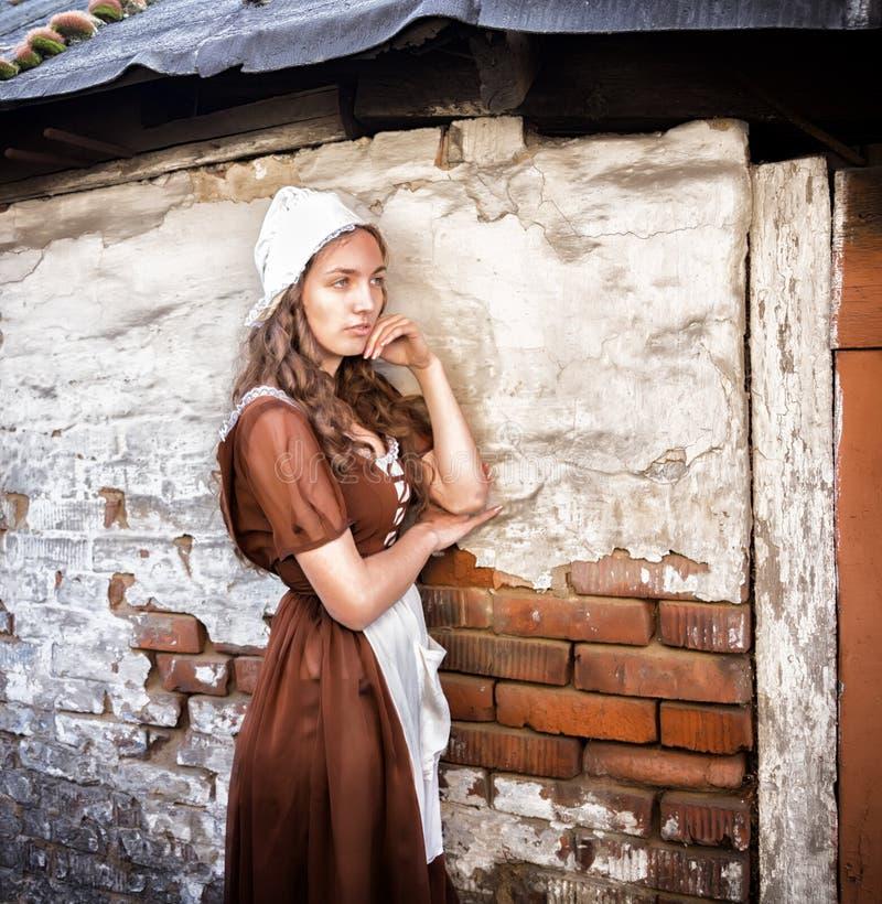 Η σκεπτική νέα γυναίκα σε ένα αγροτικό φόρεμα που στέκεται κοντά στον παλαιό τουβλότοιχο στο παλαιό σπίτι αισθάνεται μόνη Ύφος Ci στοκ φωτογραφίες