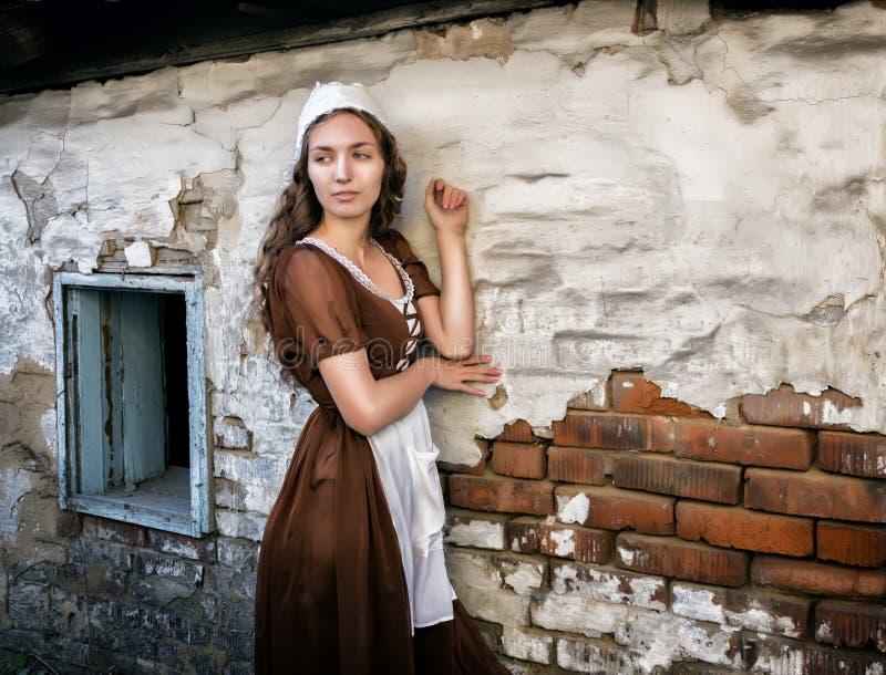 Η σκεπτική νέα γυναίκα σε ένα αγροτικό φόρεμα που στέκεται κοντά στον παλαιό τουβλότοιχο στο παλαιό σπίτι αισθάνεται μόνη Ύφος Ci στοκ εικόνες