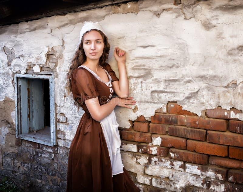 Η σκεπτική νέα γυναίκα σε ένα αγροτικό φόρεμα που στέκεται κοντά στον παλαιό τουβλότοιχο στο παλαιό σπίτι αισθάνεται μόνη Ύφος Ci στοκ φωτογραφία με δικαίωμα ελεύθερης χρήσης