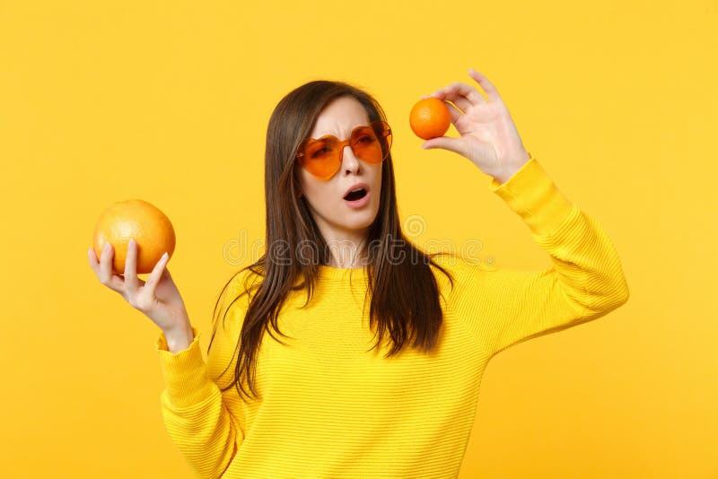Η σκεπτική νέα γυναίκα στα γυαλιά καρδιών που κρατά στα χέρια το φρέσκο ώριμο μανταρίνι, πορτοκαλιά φρούτα απομόνωσε στο κίτρινο  στοκ φωτογραφίες